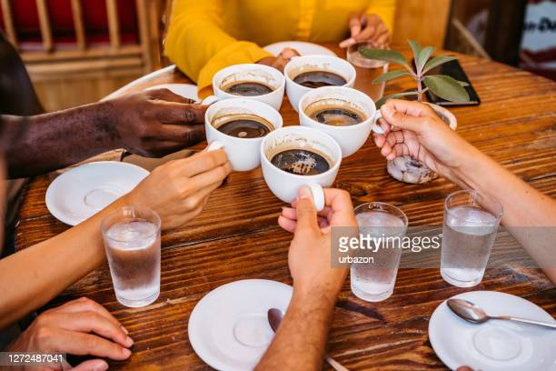 friends toasting coffee drink at coffee shop - coffee drink stock pictures, royalty-free photos & images