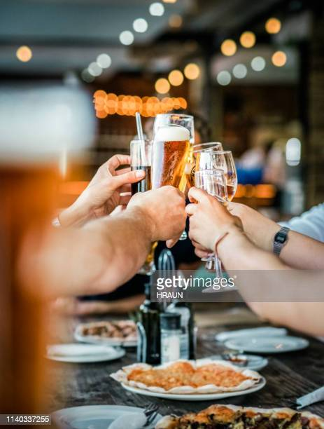 friends toasting drinks at party in restaurant - happy hour stock pictures, royalty-free photos & images