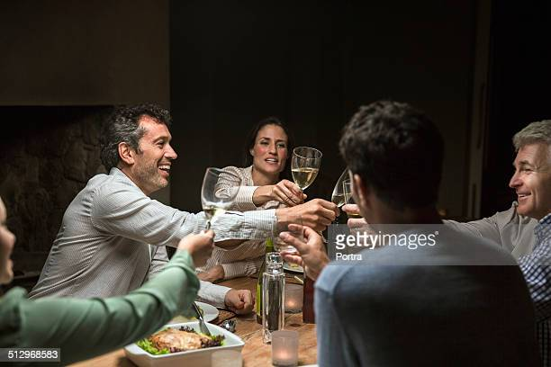 friends toasting drinks over table - brindisi bicchieri foto e immagini stock