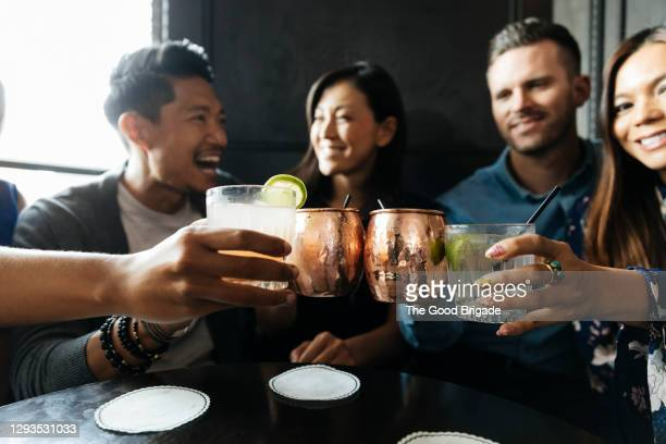 friends toasting drinks while sitting in restaurant - cocktail party stock pictures, royalty-free photos & images