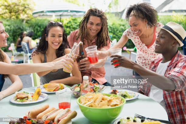 Friends toasting each other at barbecue outdoors
