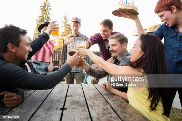Friends toasting each other with beer at birthday party