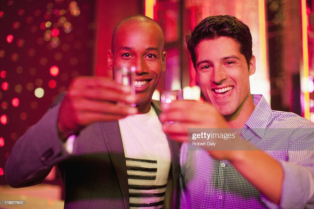 Friends toasting glasses in nightclub : Stock Photo
