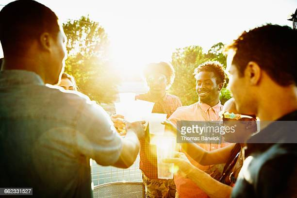 friends toasting glasses while celebrating on deck - men friends beer outside stock pictures, royalty-free photos & images