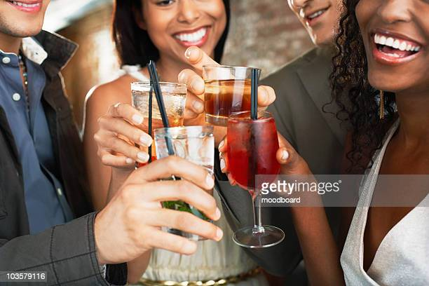 Friends toasting  in bar, close up on glasses
