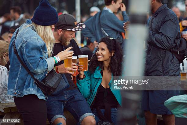 Friends toasting in beer at outside festival