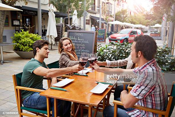 friends toasting in redwine at restaurant - klaus vedfelt mallorca stock pictures, royalty-free photos & images