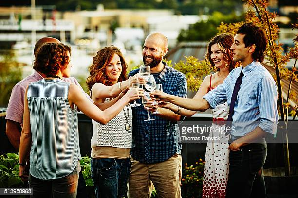 Friends toasting on rooftop deck at sunset