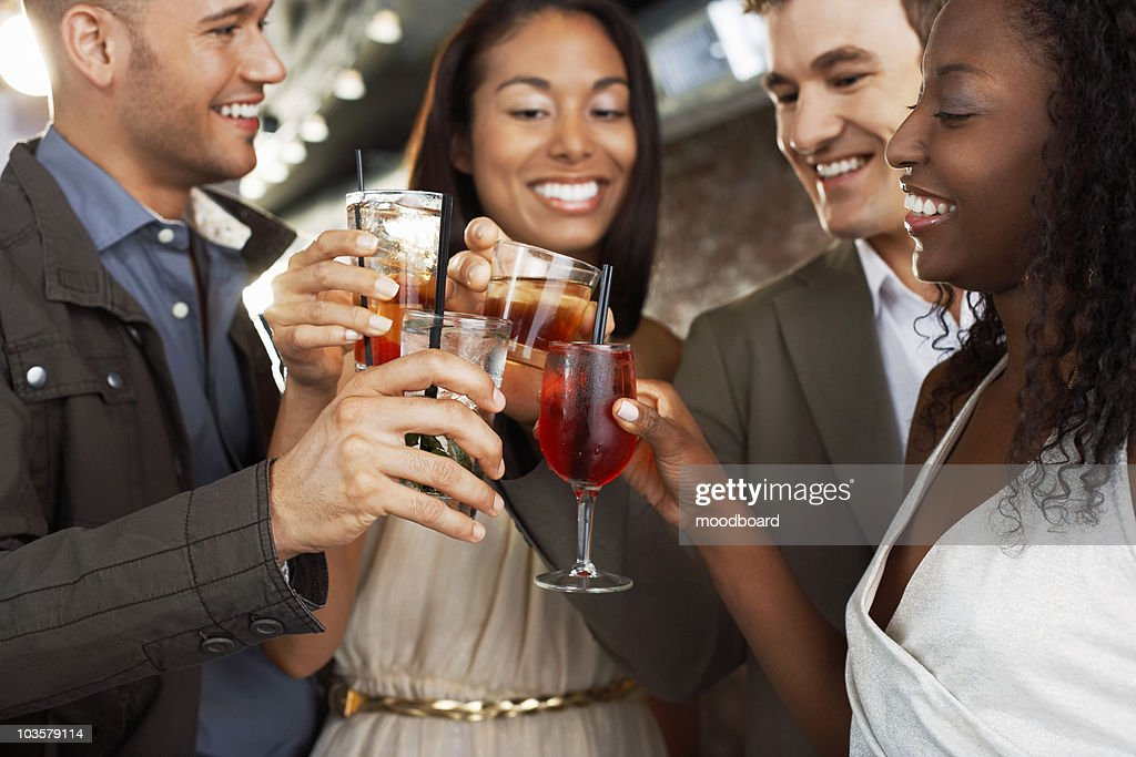 Friends toasting standing at bar : Stock Photo