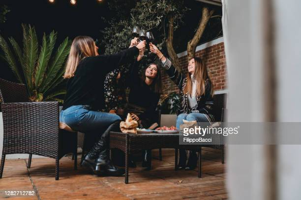 friends toasting together with red wine during a patio dinner aperitif - reopening stock pictures, royalty-free photos & images