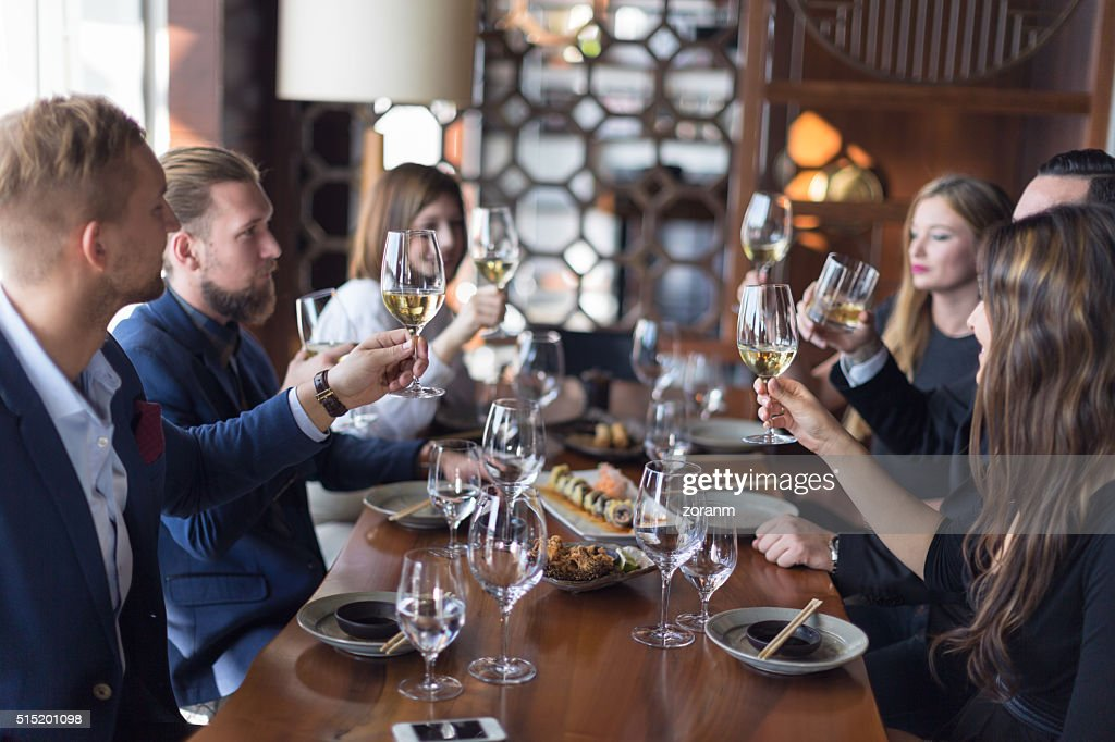 Friends toasting wine in restaurant : Stock Photo