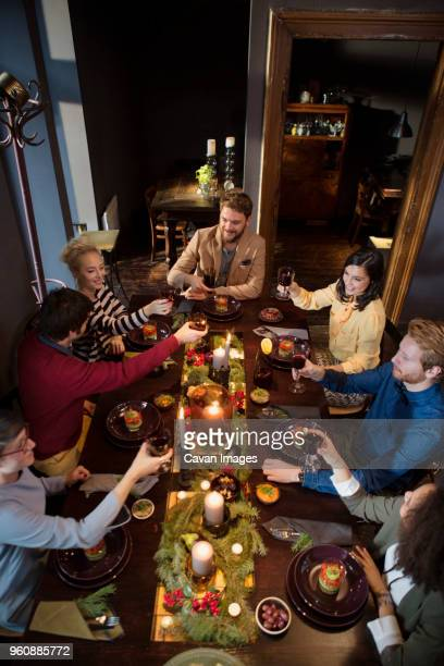 Friends toasting wine while enjoying meal during Christmas