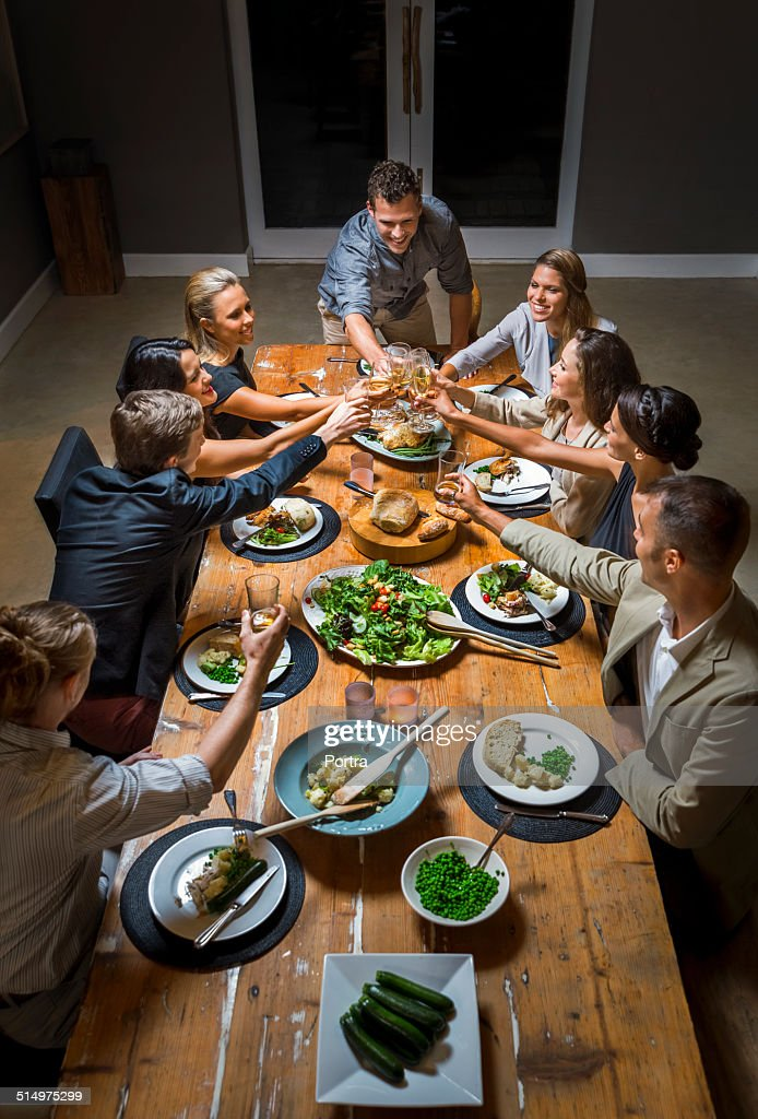 Friends toasting wineglasses at dinner table : Stock-Foto