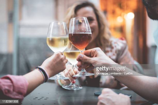 friends toasting wineglasses in restaurant - vin photos et images de collection