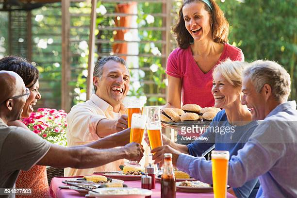 Friends toasting with beer at backyard barbecue
