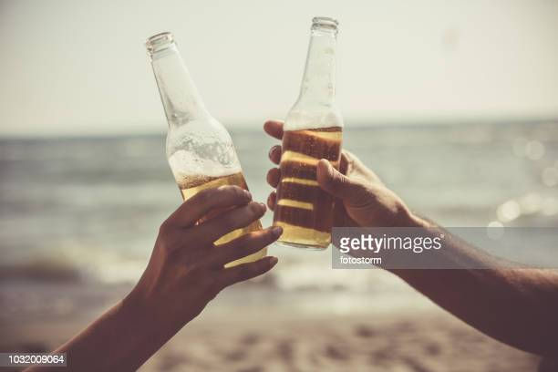 friends toasting with beer bottles at the beach - honour stock pictures, royalty-free photos & images