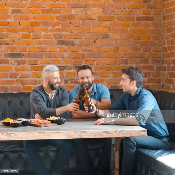 Friends toasting with beer bottles in the pub