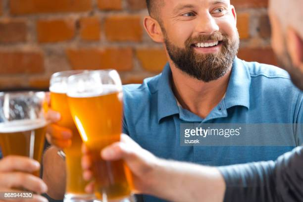 friends toasting with beer glasses in the pub - izusek stock pictures, royalty-free photos & images