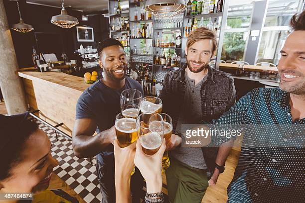 amigos de tostar com cerveja em um pub - izusek imagens e fotografias de stock