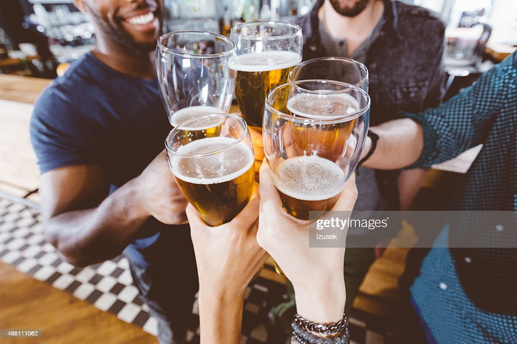 Friends toasting with beer in a pub : Stock Photo