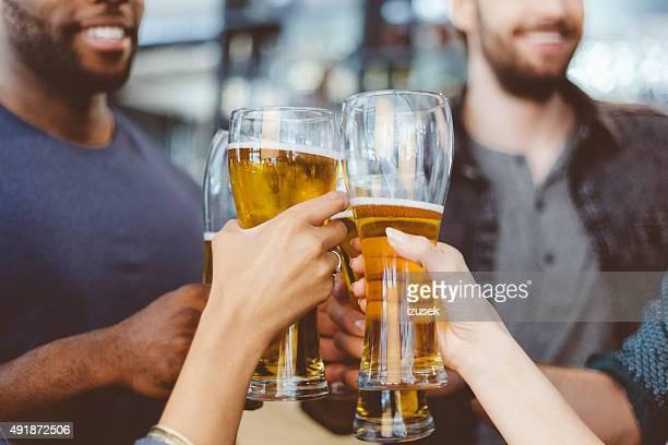 Brindis de amigos con una cerveza en el bar