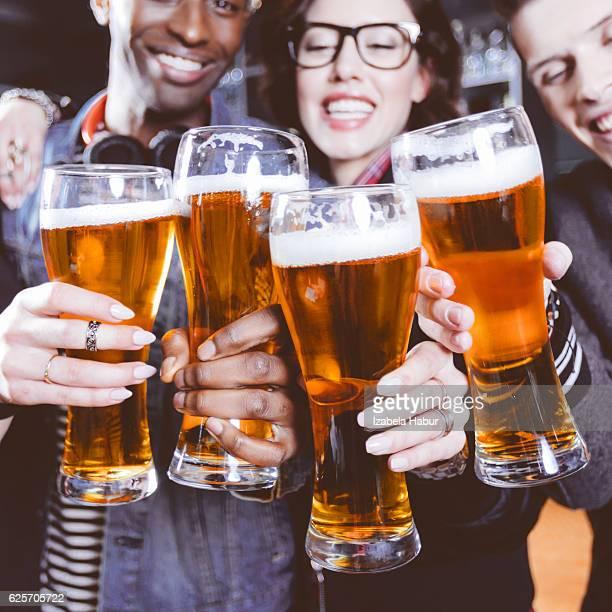 Amis portant un toast à la bière dans un pub