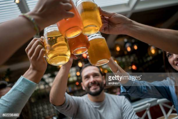Friends toasting with beers at a restaurant