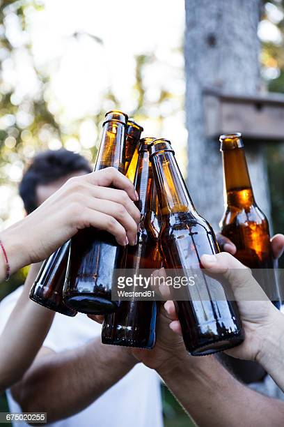 friends toasting with bottles of beer - ビール瓶 ストックフォトと画像