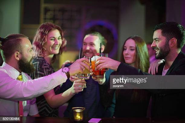 Friends toasting with drinks in bar