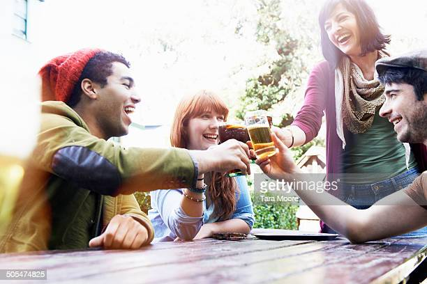friends toasting with drinks in beer garden - men friends beer outside stock pictures, royalty-free photos & images