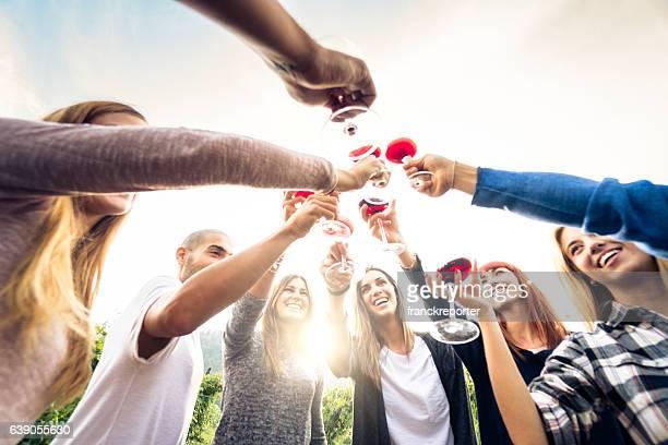 Freunden anstoßen mit Rotwein nach der Ernte