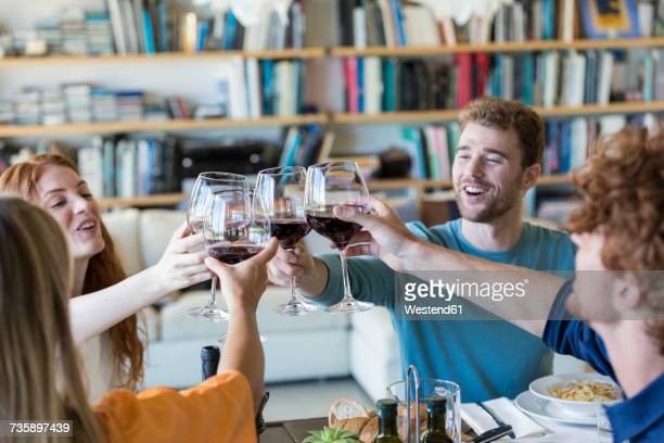 friends toasting with red wine - four people foto e immagini stock