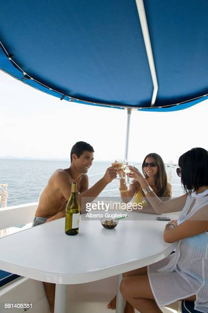 Friends toasting with white wine on sailboat deck