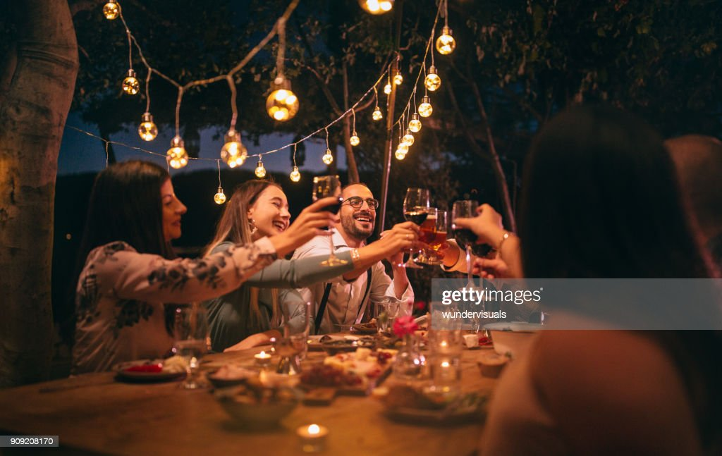 Friends toasting with wine and beer at rustic dinner party : Stock Photo