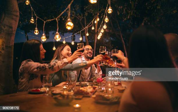 friends toasting with wine and beer at rustic dinner party - outdoors stock pictures, royalty-free photos & images