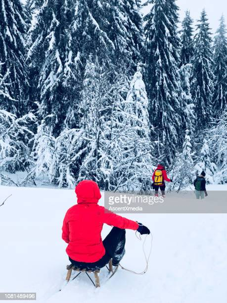 friends toboggan through snow - red coat stock pictures, royalty-free photos & images