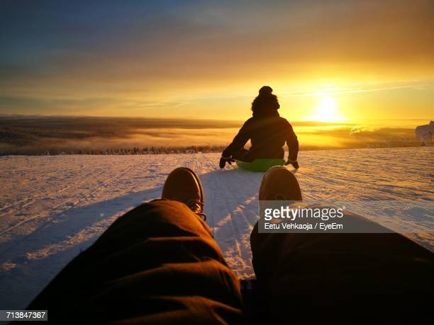 friends tobogganing on snow covered hill against orange sky - low section stock pictures, royalty-free photos & images