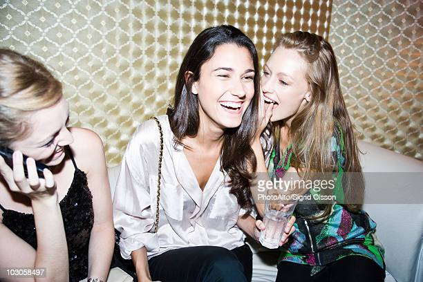 Friends together at night club, women gossiping