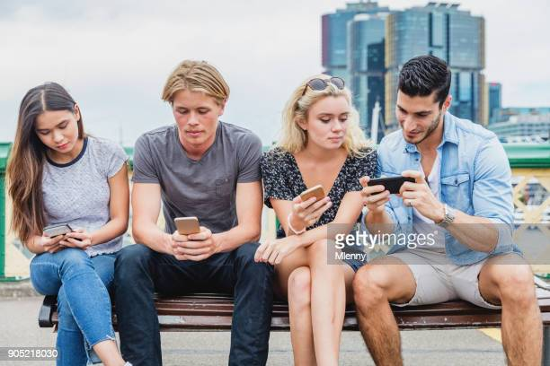 friends together checking smart phone messages darling harbour sydney - 20 24 years stock pictures, royalty-free photos & images