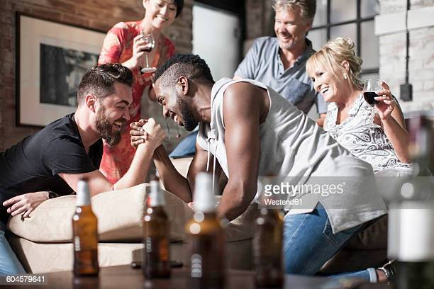 Friends together having a good time arm wrestling