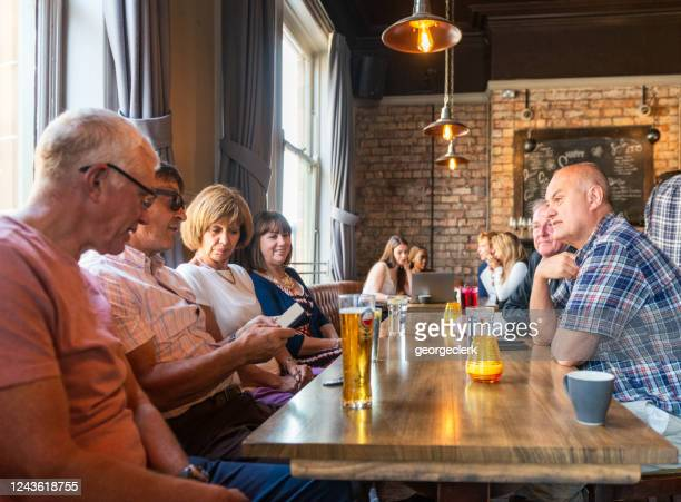 friends together in a british pub - pub stock pictures, royalty-free photos & images