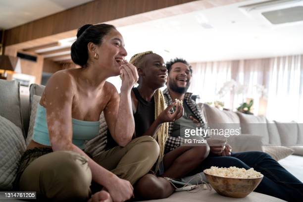 friends together watching tv at home - spectator stock pictures, royalty-free photos & images