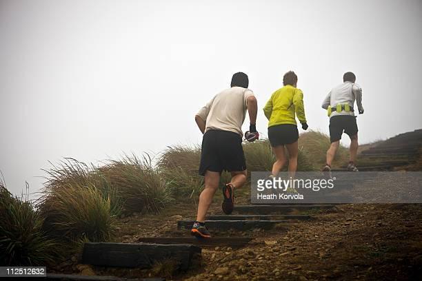 Friends trail running through thick fog.