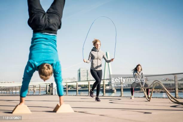friends training at the riverside, skipping rope and doing handstand - köln stock-fotos und bilder