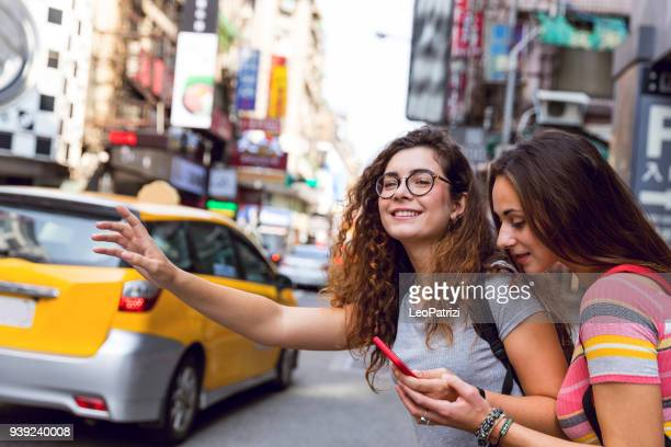 friends traveling abroad to asia waiting for a taxi on the street - hail stock pictures, royalty-free photos & images