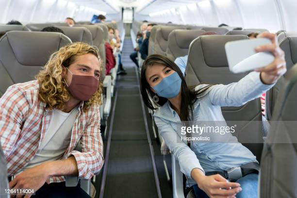 friends traveling by plane wearing facemasks and taking a selfie - biosecurity stock pictures, royalty-free photos & images