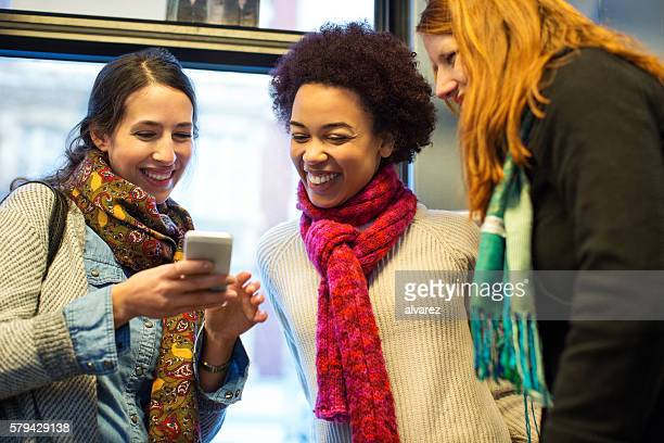 Friends traveling by train using mobile phone