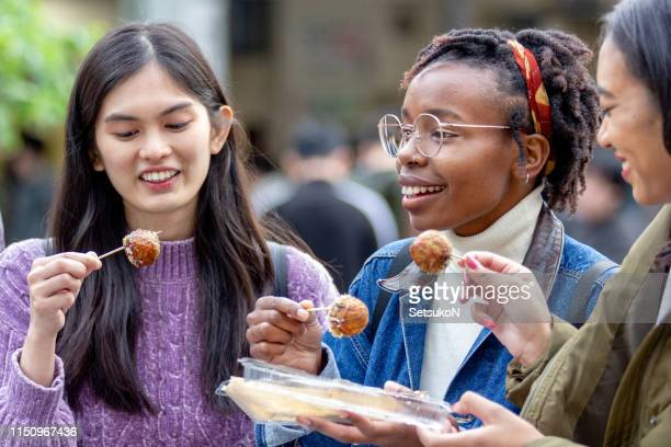 friends traveling in japan, exploring in tokyo - takoyaki stock pictures, royalty-free photos & images