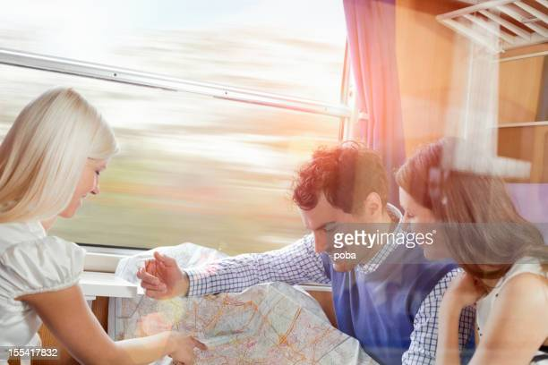 friends traveling with train and looking at the map