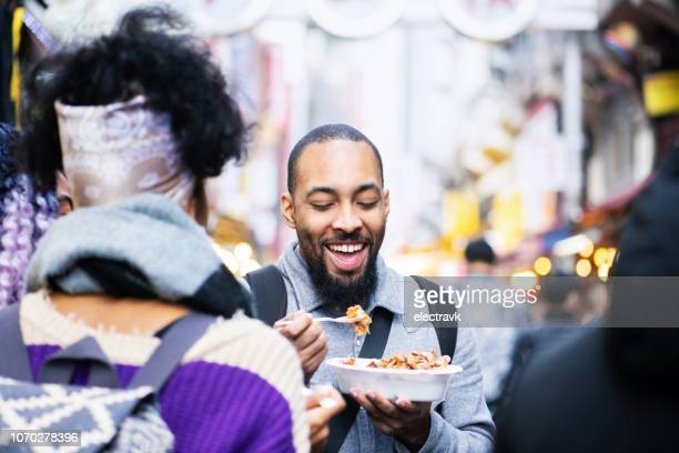 friends trying local delicacies while exploring their destination - street food stock pictures, royalty-free photos & images